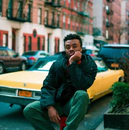 Mann sitzt vor gelbem Auto